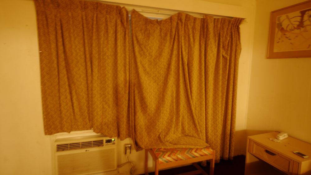 レールが壊れたカーテンからわずかな光が差し込む