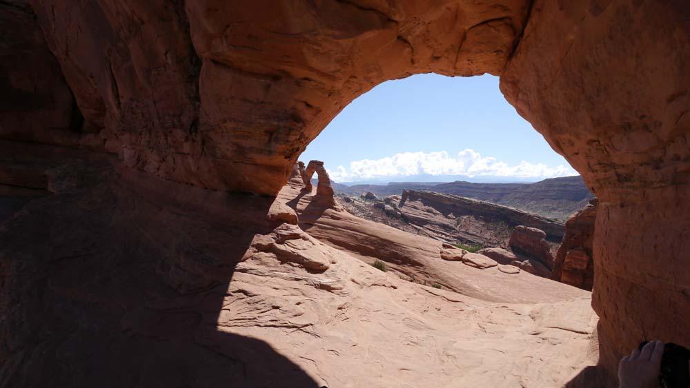 登ってみてみると、穴の向こうにデリケートアーチが望める